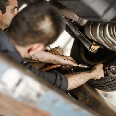 men working underneath car