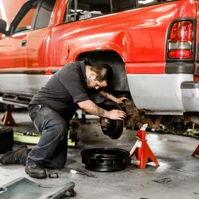 man working on a trucks brakes